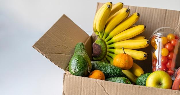 La caisse avec des fruits crus frais à envoyer comme don aux enfants pauvres