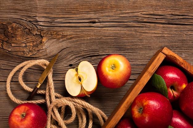 Caisse plate avec des pommes mûres avec une corde