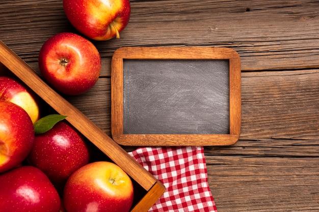 Caisse plate avec pommes mûres et tableau noir