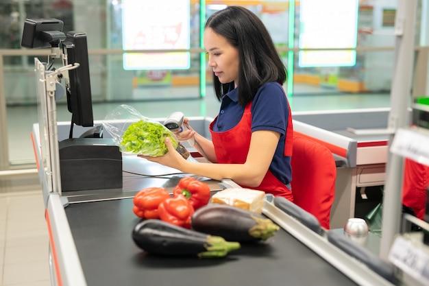 Caissier asiatique attrayant portant un tablier rouge vendant des légumes frais au client
