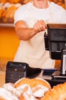 Caissier au travail. close-up of male caissier glisse une carte en plastique à travers une machine tout en se tenant dans la boulangerie
