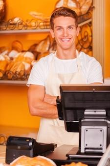 Caissier en boulangerie. beau jeune caissier en tablier gardant les bras croisés et souriant tout en se tenant à la caisse enregistreuse de la boulangerie