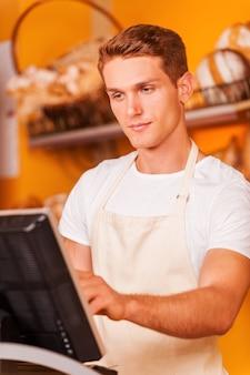 Caissier confiant au travail. beau jeune caissier en tablier travaillant avec une caisse enregistreuse en se tenant debout dans une boulangerie