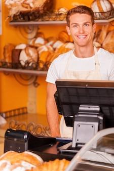 Caissier confiant. beau jeune caissier en tablier debout près de la caisse enregistreuse et souriant en se tenant debout dans une boulangerie