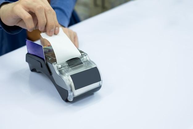 Caissier du personnel déchirer le papier avec la carte sur le terminal de paiement