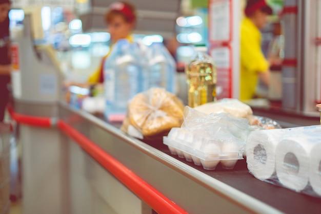Caissier de supermarché avec de la nourriture sur le convoyeur à acheter le week-end