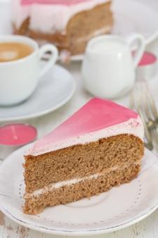 Cake sur assiette blanche et tasse de café sur bois blanc