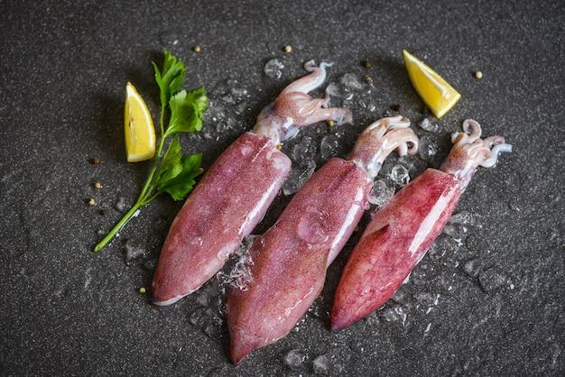 Calamars crus sur glace avec du citron sur le marché de fruits de mer assiette sombre / poulpe de calamars frais ou seiche pour restaurant de salade d'aliments cuits