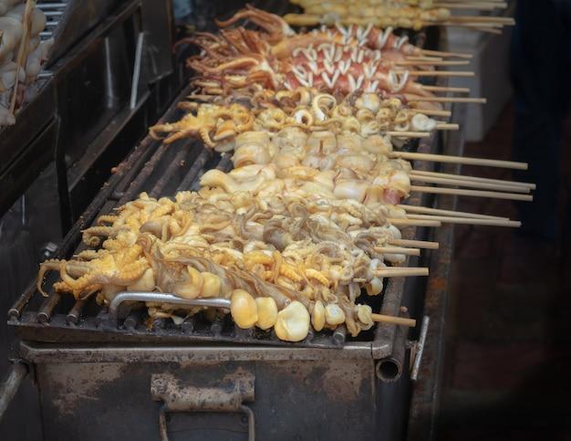 Calamars frais en brochettes et grillés au charbon de bois. fruits de mer prêts à manger.