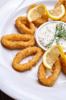 Calamars frits dans la chapelure sauce tartare au citron vue de côté à l'aneth