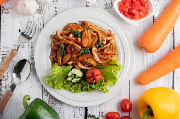 Calamars frits avec de la pâte de curry dans une assiette blanche, avec des légumes et des accompagnements sur un plancher en bois blanc.