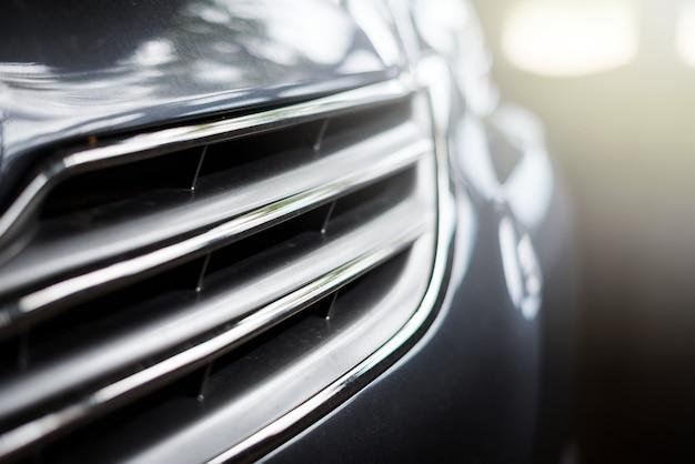 Calandre de voiture avant une couleur noire avec reflet juste lumière et arrière-plan flou