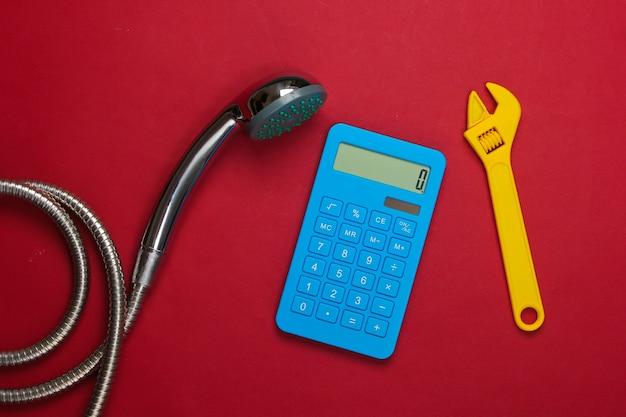Calcul des coûts de plomberie. calculatrice, pomme de douche avec un tuyau, clé sur rouge.