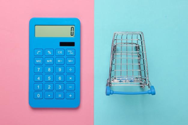 Calcul des coûts pour les courses, les achats au supermarché. calculatrice et caddie sur fond bleu rose. vue de dessus. minimalisme