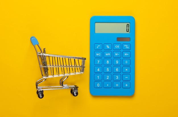 Calcul des coûts pour les courses, les achats au supermarché. calculatrice et caddie sur fond jaune. vue de dessus. minimalisme