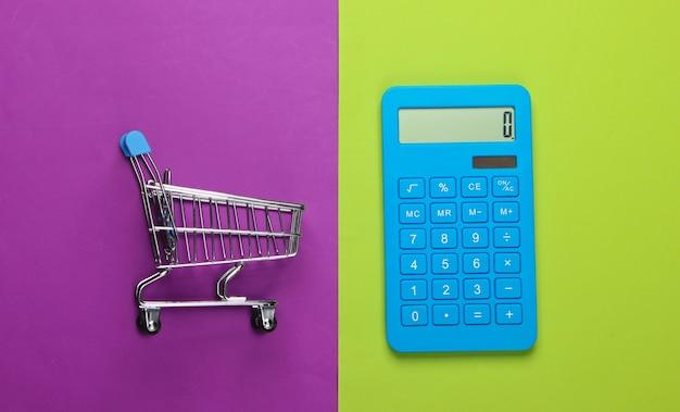 Calcul des coûts pour les courses, les achats au supermarché. calculatrice et caddie sur fond vert-violet. vue de dessus. minimalisme