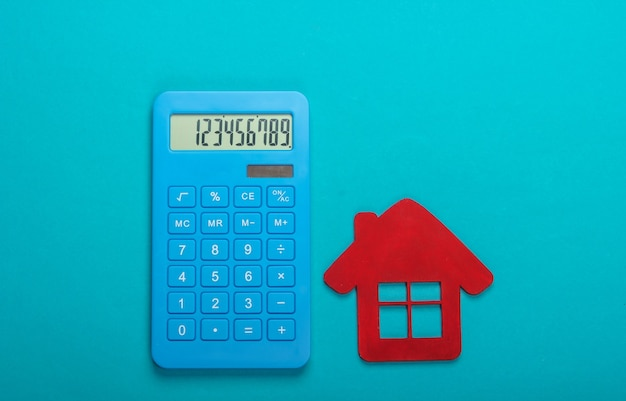 Calcul du coût du logement locatif. figurine de maison rouge, calculatrice sur fond bleu. vue de dessus