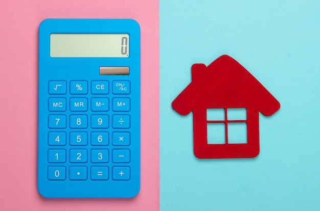 Calcul du coût du logement locatif. figurine maison rouge, calculatrice sur fond pastel bleu rose. vue de dessus