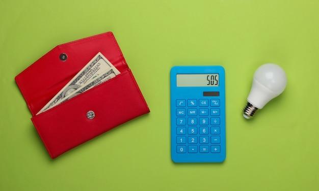 Calcul du coût des frais médicaux. calculatrice et bouteille de pilules, portefeuille avec de l'argent sur fond vert. vue de dessus. minimalisme