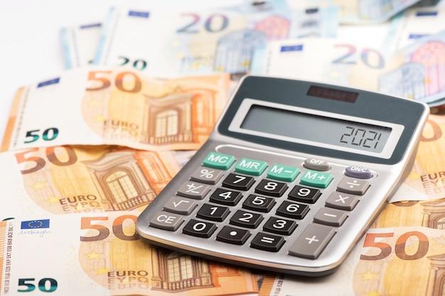 Une calculatrice avec de l'argent en euros affichant l'année d'imposition 2021