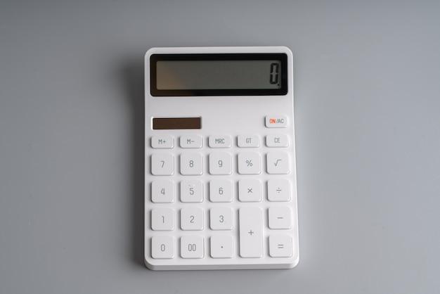 Calculatrice blanche sur fond gris pour l'éducation et le concept d'entreprise