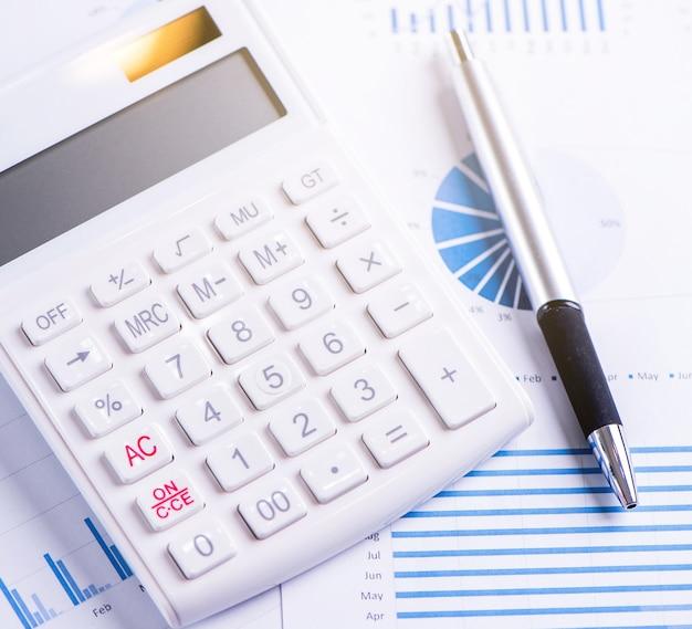 Calculatrice blanche et rapport avec graphique et graphique, concept d'aperçu des bénéfices financiers annuels, banque et investissement