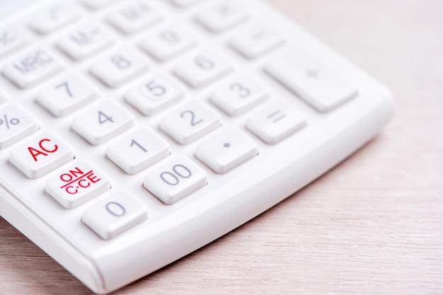 Calculatrice blanche et stylo sur table en bois clair analytique et statistiques du profit financier investissement risque concept copie espace macro close up