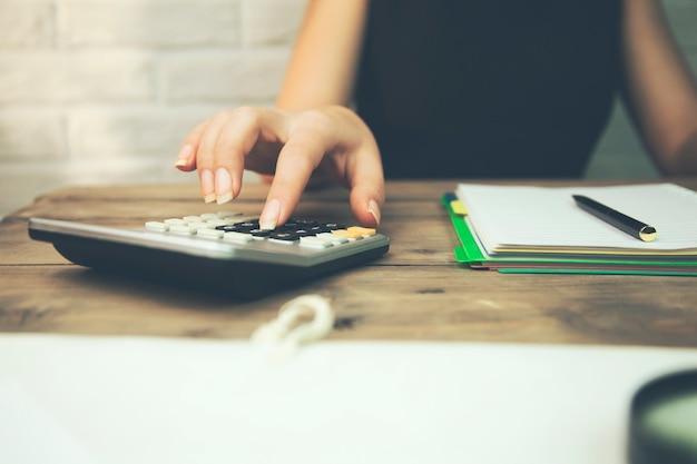 Calculatrice et bloc-notes de main de femme