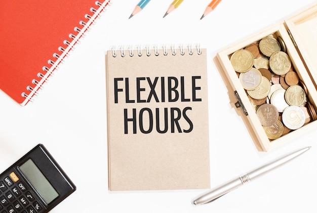 Calculatrice, bloc-notes rouge, trois crayons de couleur, stylo argenté et carnet marron avec texte heures flexibles. mise à plat