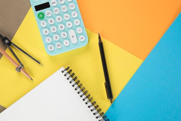 Sur la calculatrice de bureau, le bloc-notes, le stylo et le pied à coulisse. papier multicolore
