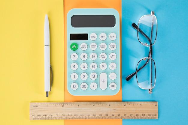 Sur la calculatrice de bureau, le stylo, les lunettes et la règle