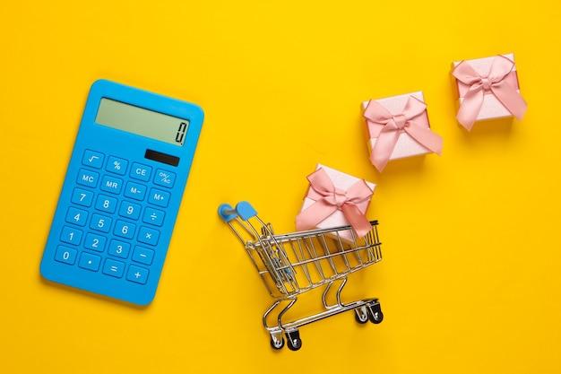 Calculatrice et caddie avec coffrets cadeaux sur jaune. calcul de la valeur du cadeau.