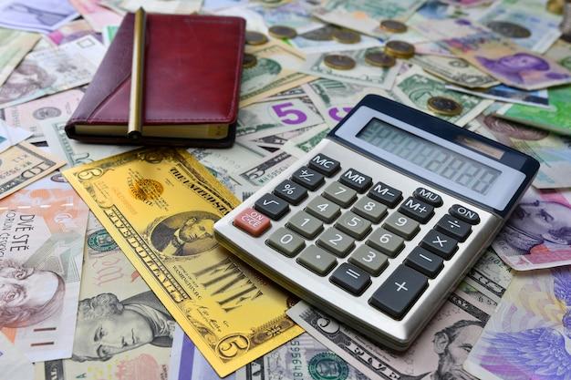 Calculatrice, cahier et crayon sur des billets de banque de pays différents et un billet de banque en dollars or symbolique. planification financière .