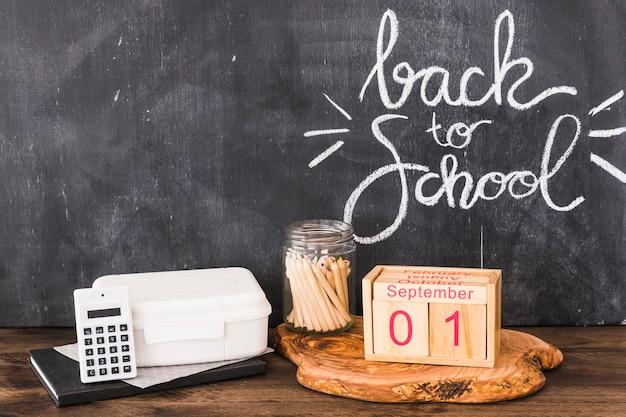 Calculatrice et calendrier près de la boîte à lunch et des crayons