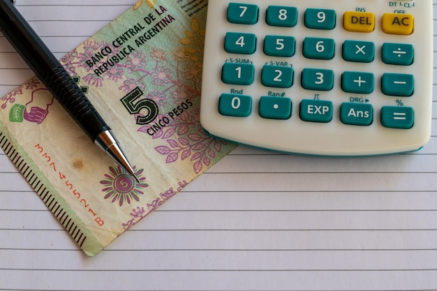 Calculatrice, cinq billets de pesos argentins sur une feuille de papier avec un crayon mécanique