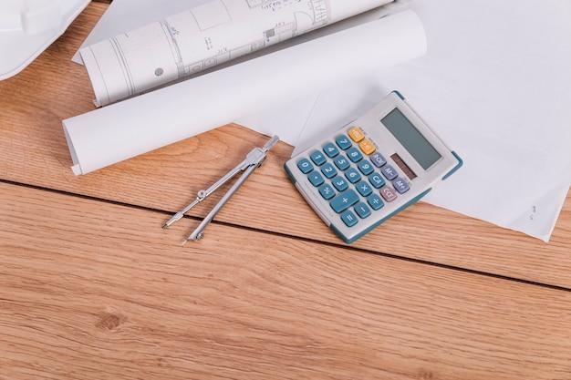 Calculatrice et compas près des plans