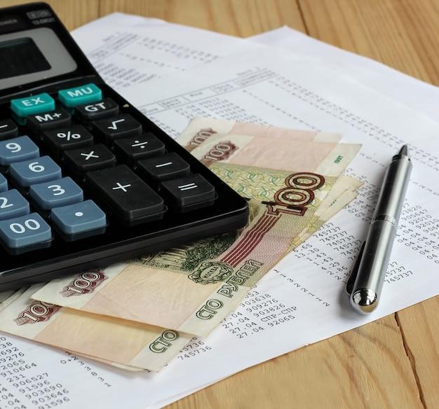 Calculatrice électronique, stylo en métal et argent russe sur des feuilles de papier avec des chiffres.