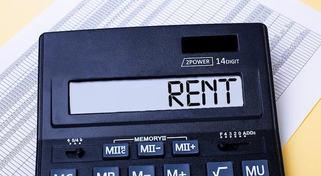Une calculatrice étiquetée rent se trouve sur la table près du rapport. concept financier