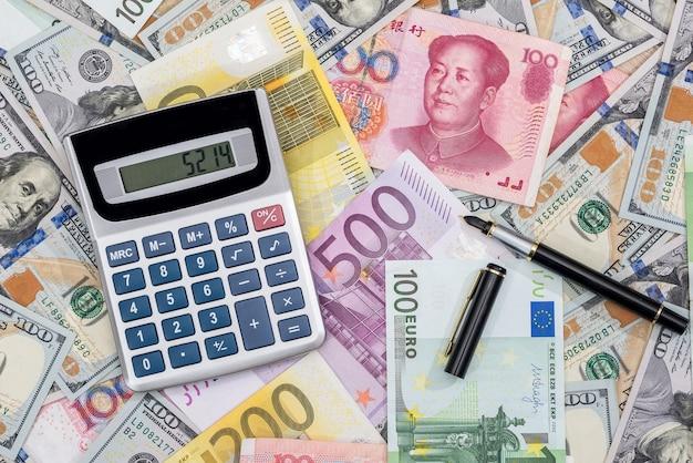Calculatrice avec euros, dolalr et yuans avec stylo sur le bureau.