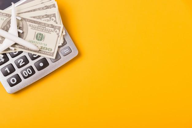 Calculatrice, factures d'argent et avion jouet