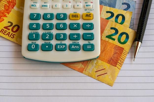 Calculatrice, factures d'argent brésilien sur une feuille de papier avec un crayon mécanique