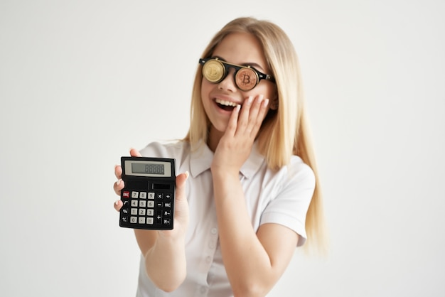 Calculatrice de femme d'affaires à la main et fond clair de bitcoin. photo de haute qualité