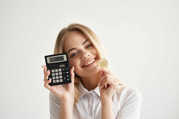 Calculatrice de femme d'affaires à la main et fond clair de bitcoin