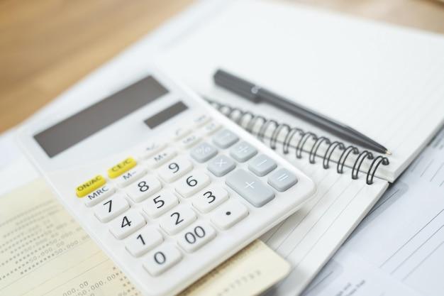 Calculatrice avec feuilles du calendrier mensuel, verres sur bois