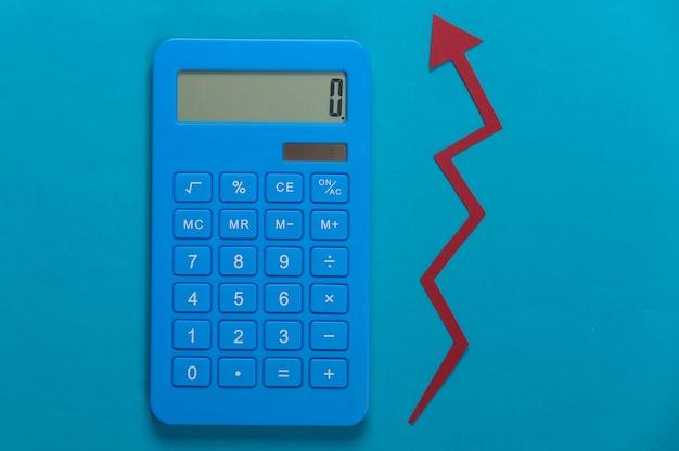 Calculatrice avec flèche de croissance rouge sur bleu. graphique de flèche qui monte. la croissance économique