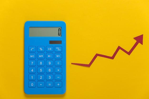 Calculatrice avec flèche de croissance rouge sur jaune. graphique de flèche qui monte. la croissance économique