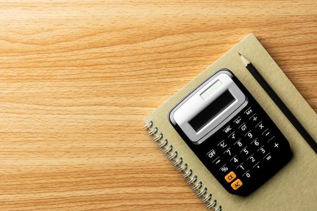 Calculatrice et fournitures de bureau sur une table en bois. - vue de dessus avec espace de copie.