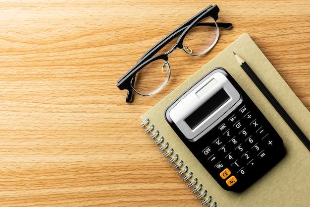 Calculatrice et fournitures de bureau sur une table en bois.