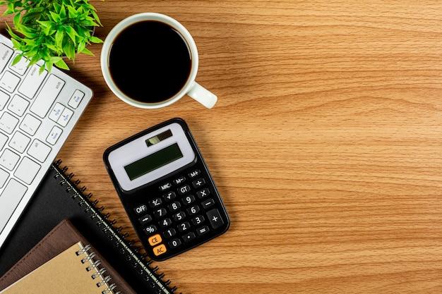Calculatrice et fournitures de bureau sur une table en bois