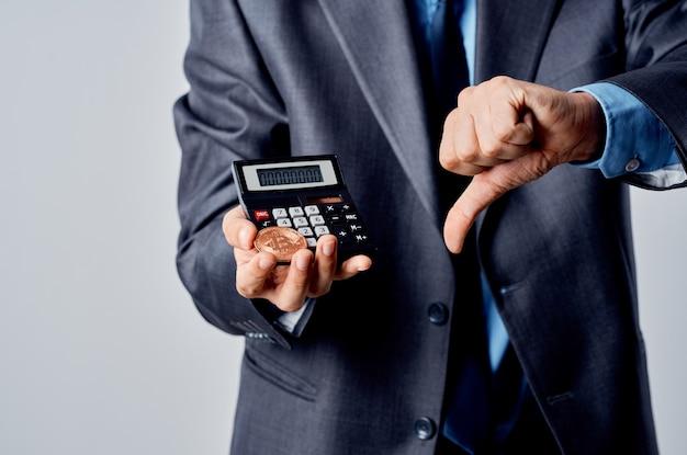 Calculatrice d'hommes d'affaires bitcoin en main comptant le fonctionnaire du studio de finance